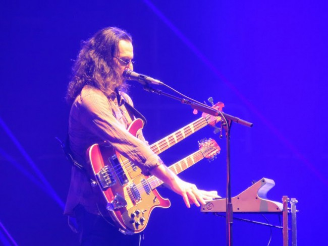 Geddy with four instruments (vocals, keys, bass, guitar)